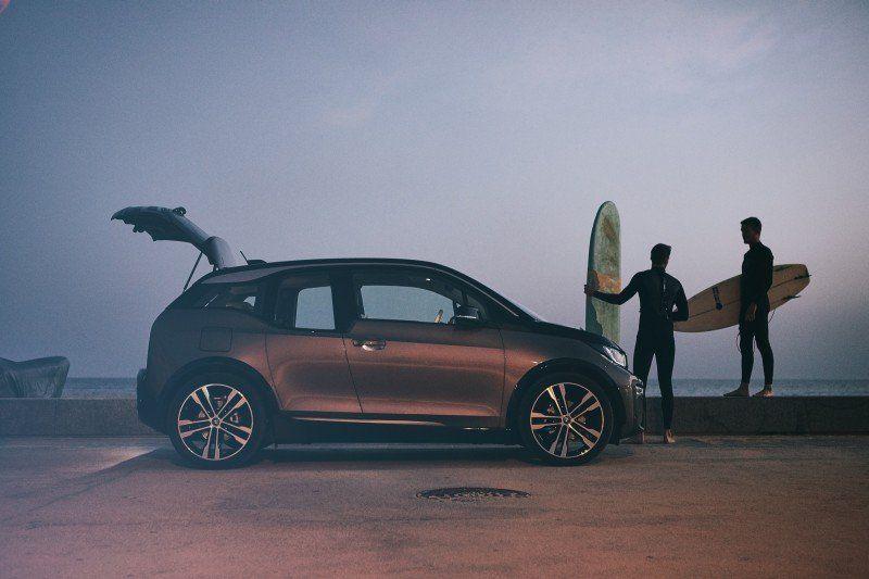 BMW i3 stehend neben zwei Surfer
