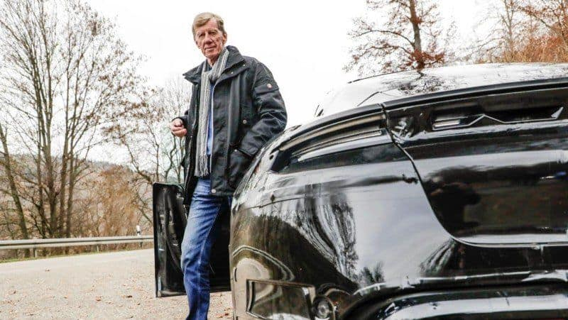Walter Röhrl an der Tür des Porsche Taycan